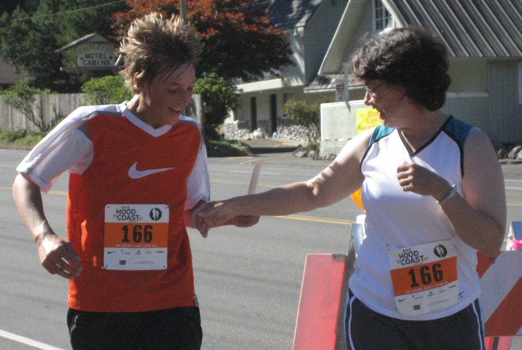 """Ross """"Roadkill"""" Priewe hands off to Scobel Wiggins during the Hood-to-Coast Relay."""
